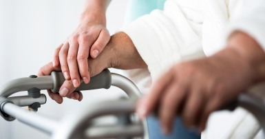 Close up on an elderly woman's hand on the handle of a walker, with a younger woman's hand resting on it gently